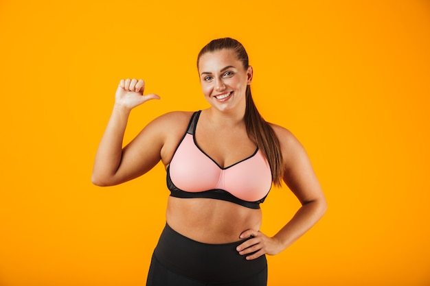 Portret van een vrolijke overgewicht fitness vrouw, gekleed in sportkleding staande geïsoleerd over gele muur, wijzend