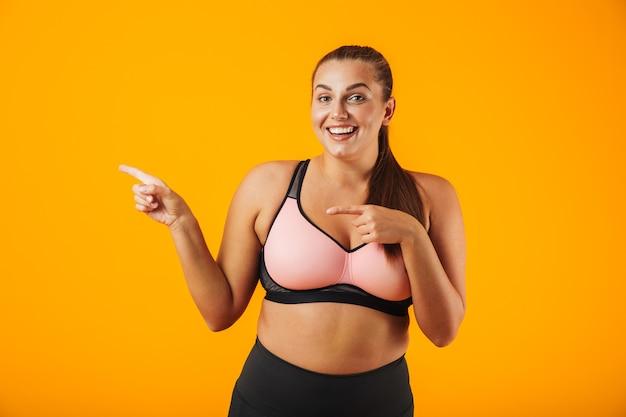 Portret van een vrolijke overgewicht fitness vrouw, gekleed in sportkleding staande geïsoleerd over gele muur, wijzende vingers naar kopie ruimte