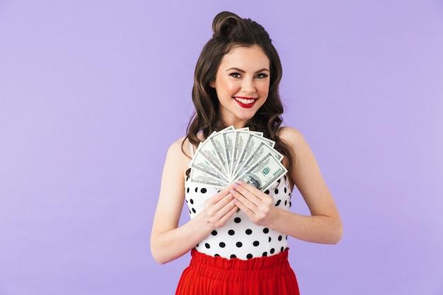 Portret van een vrolijke pin-up vrouw in vintage polka dot jurk glimlachend terwijl ze een bos geld bankbiljetten vasthoudt die over een violette muur worden geïsoleerd