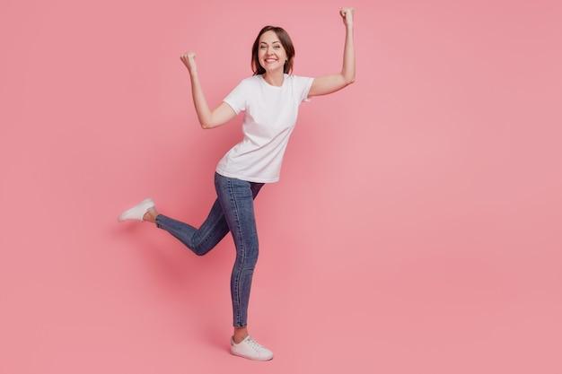 Portret van een vrolijke, prachtige winnaarsdame die vuisten opheft, veel plezier op roze achtergrond