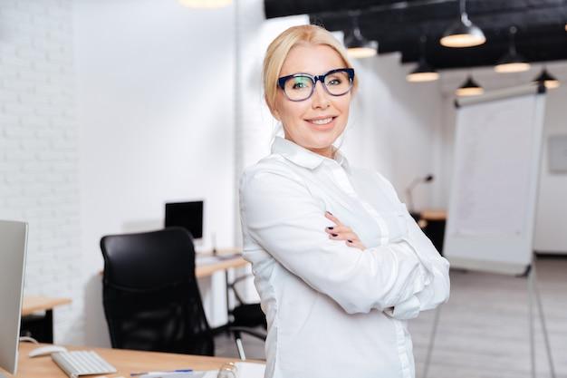 Portret van een vrolijke rijpe bedrijfsvrouw die zich met wapens bevindt die in bureau worden gevouwen
