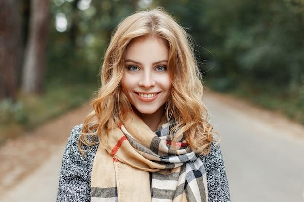 Portret van een vrolijke schattige jonge vrouw met een glimlach met blauwe ogen in een elegante jas met een geruite stijlvolle sjaal in het park tussen groene bomen