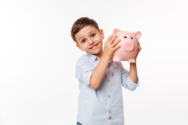 Portret van een vrolijke schattige kleine jongen bedrijf spaarvarken