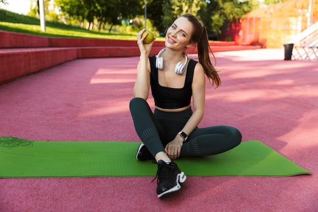 Portret van een vrolijke sportieve vrouw die een trainingspak draagt dat glimlacht en groene appel vasthoudt terwijl ze op een fitnessmat zit in een groen park