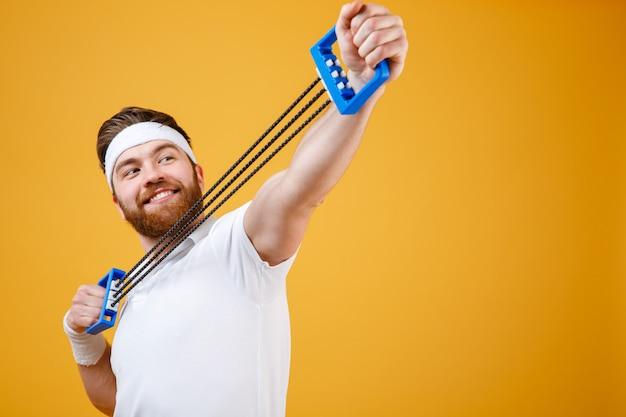 Portret van een vrolijke sportman die geschiktheidsoefeningen met expander doet