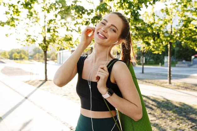Portret van een vrolijke sportvrouw die een trainingspak draagt dat naar muziek luistert met oortelefoons en een fitnessmat draagt tijdens een wandeling door het stadspark
