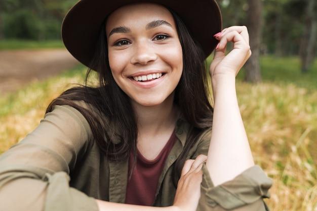 Portret van een vrolijke stijlvolle vrouw met lang donker haar met een hoed die naar de camera glimlacht terwijl ze buiten op het gras zit