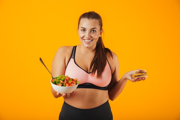 Portret van een vrolijke te zware fitnessvrouw die sportkleding draagt die zich geïsoleerd over gele muur bevindt, die kom met salade en een hamburger houdt