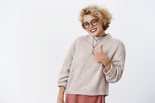 Portret van een vrolijke, tevreden en onder de indruk knappe, charmante, vrolijke blonde vrouw met een bril en een trui die duim omhoog laat zien en flirterig knipoogt, leuk vindt en akkoord gaat met een geweldig plan.