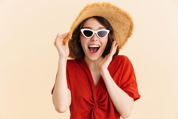 Portret van een vrolijke verbaasde vakantievrouw met een strohoed en een modieuze zonnebril die zich verheugt