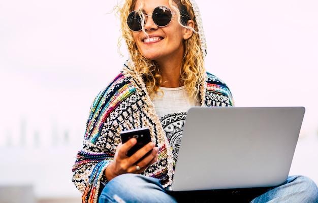 Portret van een vrolijke volwassen blanke vrouw die buiten werkt met telefoon en laptopcomputer in roamingtechnologie