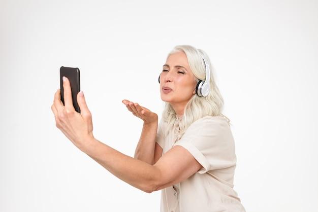 Portret van een vrolijke volwassen vrouw in koptelefoon