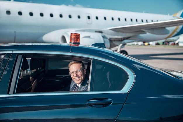 Portret van een vrolijke volwassen zakenman die uit het raam kijkt terwijl hij aankomt op de startbaan om in te stappen