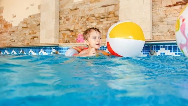 Portret van een vrolijke, vrolijke peuterjongen die speelt met een opblaasbare strandbal en een kleurrijke ring bij het binnenzwembad in huis