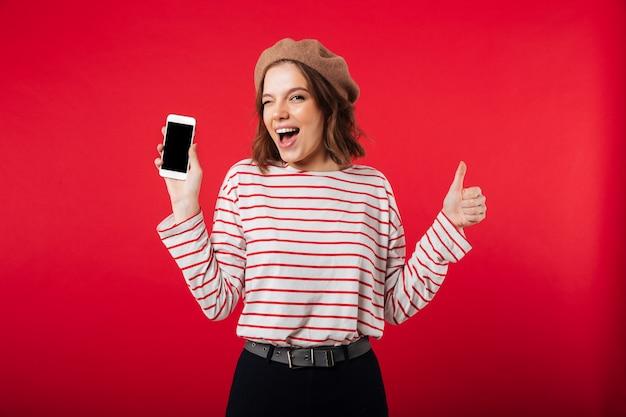 Portret van een vrolijke vrouw die baret draagt