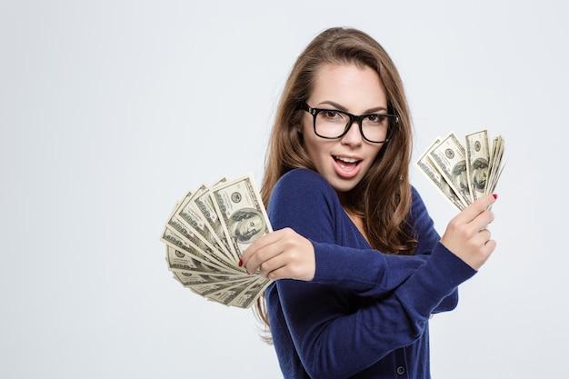 Portret van een vrolijke vrouw die dollarbiljetten vasthoudt en naar camera kijkt die op een witte achtergrond wordt geïsoleerd