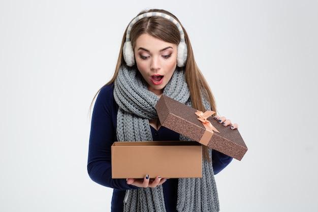 Portret van een vrolijke vrouw die een geschenkdoos opent die op een witte achtergrond wordt geïsoleerd