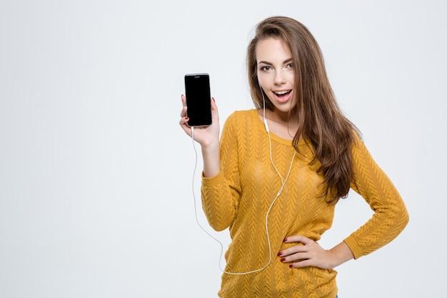Portret van een vrolijke vrouw die een leeg smartphonescherm toont dat op een witte achtergrond wordt geïsoleerd