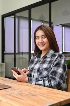 Portret van een vrolijke vrouw die een mobiele telefoon vasthoudt en naar de camera glimlacht.