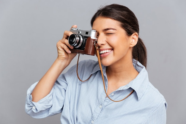 Portret van een vrolijke vrouw die foto maakt met voorkant geïsoleerd op een grijze muur