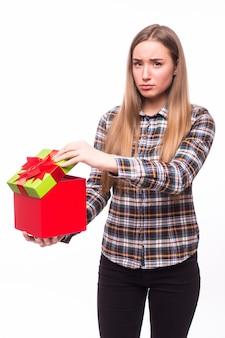 Portret van een vrolijke vrouw die geschenkdoos opent die op een witte muur wordt geïsoleerd
