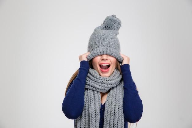 Portret van een vrolijke vrouw die haar ogen bedekt met een hoed geïsoleerd op een witte muur