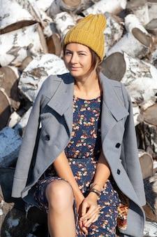 Portret van een vrolijke vrouw in een gebreide muts, jas, mooie jurk en laarzen, glimlacht schattig, poseert, glimlacht en zit op berkenhout.