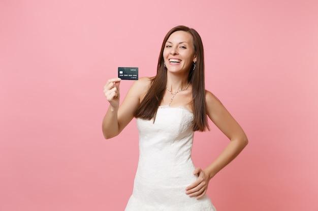 Portret van een vrolijke vrouw in een mooie kanten witte jurk met een creditcard