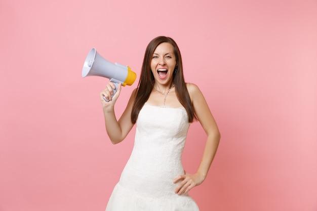 Portret van een vrolijke vrouw in witte kanten witte jurk die schreeuwt en een megafoon vasthoudt