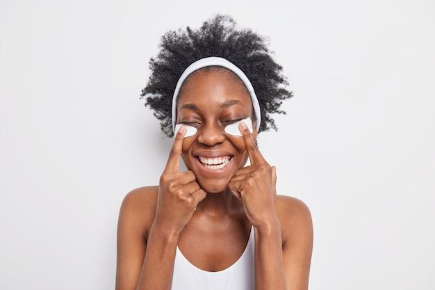 Portret van een vrolijke vrouw met een donkere huid lacht breed en wijst naar schoonheidspleisters sluit de ogen