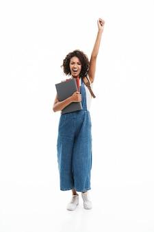 Portret van een vrolijke vrouw met een rugzak die de arm opheft en zich verheugt terwijl ze boeken vasthoudt die over een witte muur zijn geïsoleerd