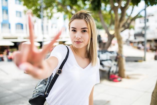 Portret van een vrolijke vrouw. mooie vrouw overwinning of vredesteken buiten in zomer straat tonen.