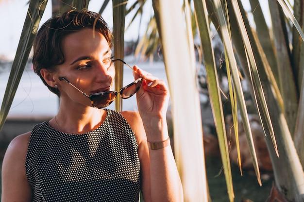 Portret van een vrouw achter palmbladen