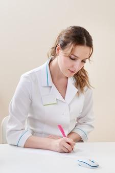 Portret van een vrouw arts die iets in haar kantoor aan een tafel in een kliniek schrijft