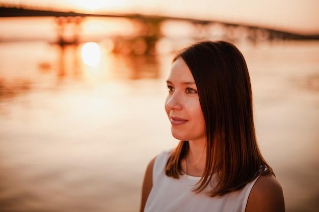 Portret van een vrouw bij zonsondergang close-up portret van een mooie jonge vrouw die geniet van de zonsondergang op een s...