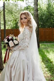 Portret van een vrouw bruid in een trouwjurk met een boeket bloemen in haar handen