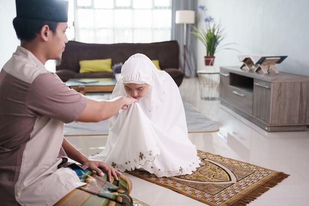 Portret van een vrouw die de hand van haar man kust na samen thuis bidden