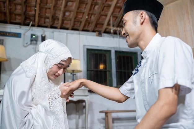 Portret van een vrouw die de hand van haar man kust nadat ze thuis samen heeft gebeden