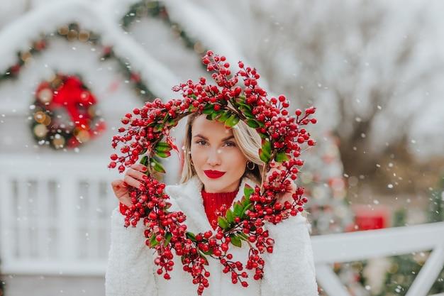Portret van een vrouw die de rode kroon van kerstmis houdt en erdoorheen kijkt.