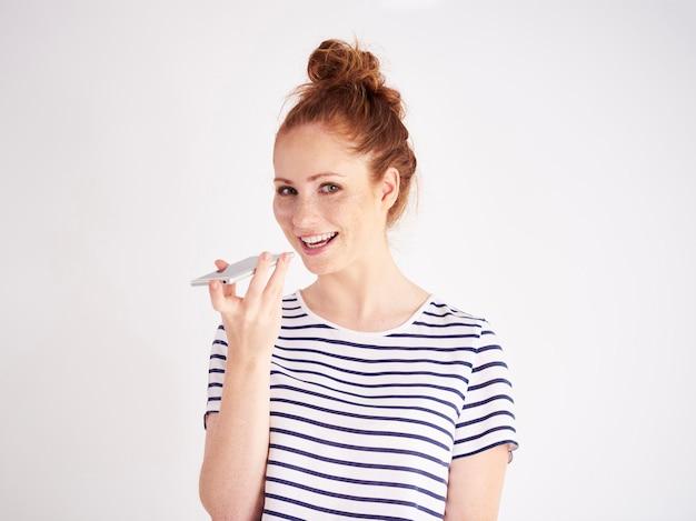 Portret van een vrouw die de spraakherkenning van een smartphone gebruikt