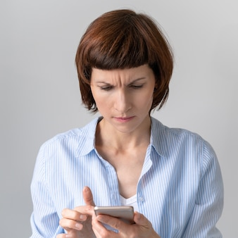 Portret van een vrouw die de verbaasde telefoon bekijkt