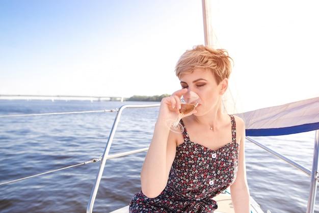 Portret van een vrouw die door overzees op een jacht op een de zomer zonnige dag drijft