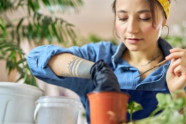 Portret van een vrouw die een bloempot voorbereidt voor een planttransplantatie die aan een bureau in de woonkamer zit