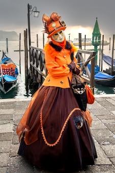 Portret van een vrouw die een carnaval-kostuum met gezichtsmasker draagt