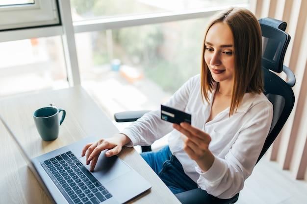 Portret van een vrouw die een creditcard vasthoudt en thuis een laptop gebruikt