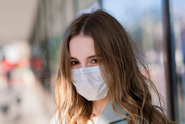 Portret van een vrouw die een medisch masker draagt en in de straat tegen een café staat, close-up