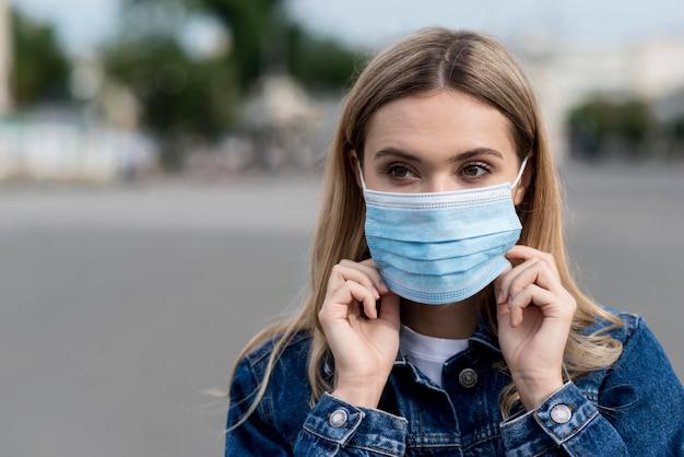 Portret van een vrouw die een medisch masker draagt