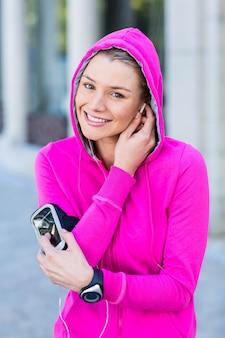 Portret van een vrouw die een roze jasje draagt dat haar hoofdtelefoons zet