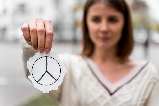Portret van een vrouw die een vredesteken houdt