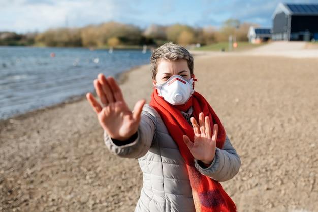 Portret van een vrouw die een wit en rood gezichtsmasker draagt, met stop buitenshuis
